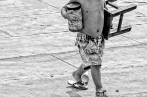 A young boy with jar and stool crosses a courtyard in Phnom Penh, Cambodia.